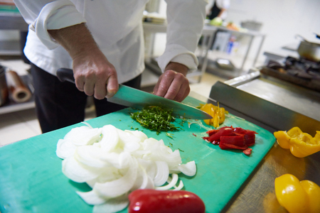 human hands: chef in hotel kitchen  slice  vegetables with knife and prepare food