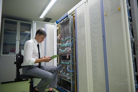 computer room: network engineer working in  server room, corporate business man working on tablet computer