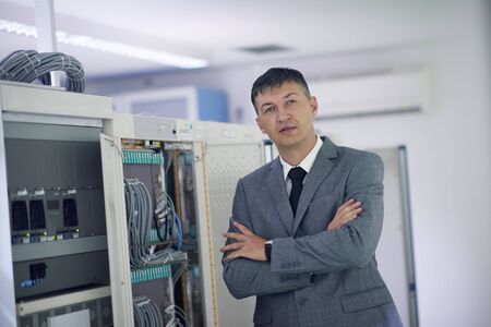 young male: network engineer working in  server room, corporate business man Stock Photo
