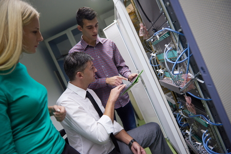 server: business people group, network engeneers working in network server room on tablet computer