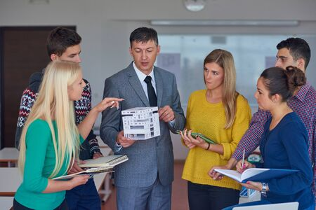 girl home: group of students working with teacher on wooden small house model Stock Photo