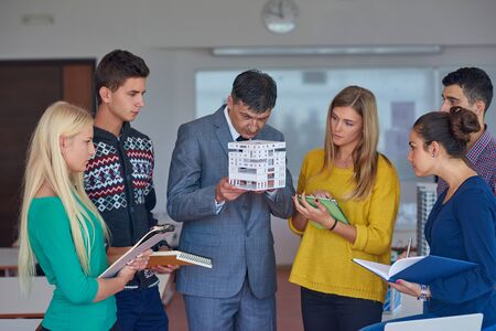 small group: group of students working with teacher on wooden small house model Stock Photo