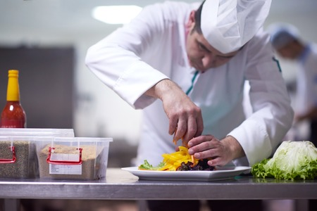 meat food: chef in hotel kitchen preparing and decorating food, delicious vegetables and meat  meal dinner Stock Photo
