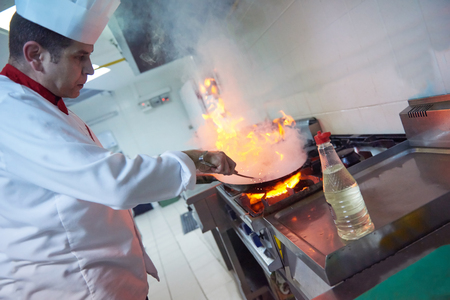 hotel kitchen: chef in hotel kitchen prepare vegetable  food with fire