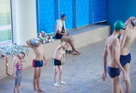 nadar: grupo de niños felices los niños en la piscina al aprendizaje de la clase de la piscina para nadar Foto de archivo