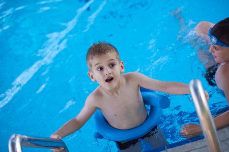 niños sonriendo: niño en piscina aprender a nadar w