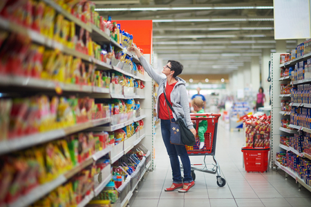 young mother with baby in shopping mall supermarket store buying food and grocery