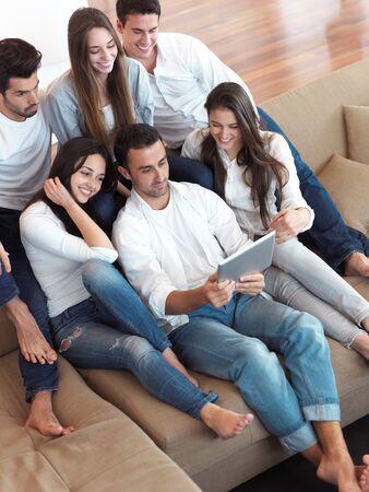 niñas bonitas: grupo de amigos que toman selfie foto con la tableta en el interior de casas modernas Foto de archivo