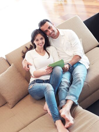 couple relaxing: romantic relaxed young couple at modern home using tablet computer