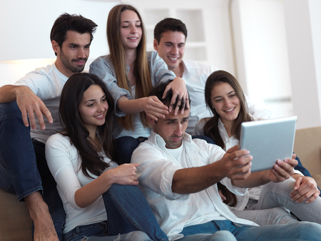 young friends: group of friends taking selfie photo with tablet at modern home indoors Stock Photo