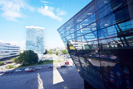 reflect: modern glass building window facade with cityscape in baclground