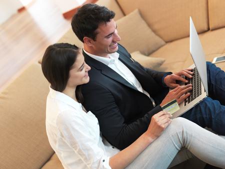 trabajando en casa: feliz pareja relajada joven que trabaja en la computadora portátil en el interior de una casa moderna Foto de archivo