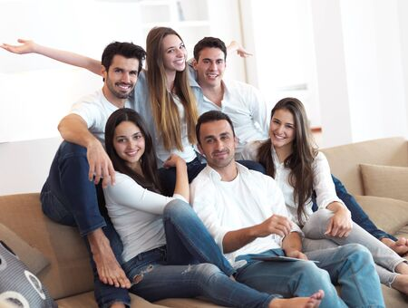 group of young adults: group of friends taking selfie photo with tablet at modern home indoors Stock Photo