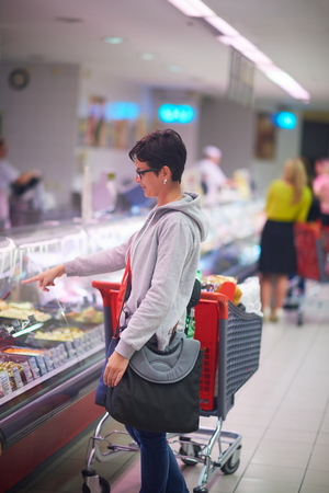 produce departments: shopping woman in supermarket store buying food and grocery