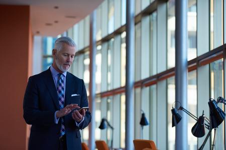 senior zakenman praten op mobiele telefoon in modern bright office interieur Stockfoto