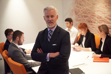 man in suit: senior businessman with his team at modern office. business people group