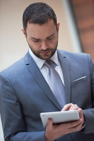 white suit: portrait of young business man with tablet computer at modern office