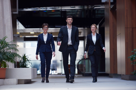 woman business suit: young business people team walking, group of people on modern office hall interior