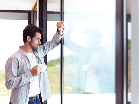 big window: relaxed young man drink first morning coffee at modern home indoors Stock Photo