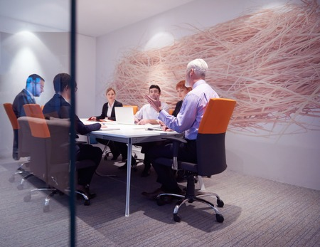 business people meeting: business people group with young adults and senior on meeting at modern bright office interior. Stock Photo