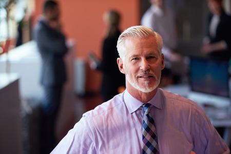Senior Geschäftsmann mit seinem Team im Büro. Geschäftsleute Gruppe
