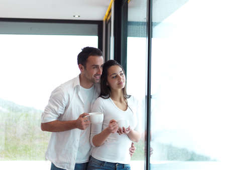 women coffee: relaxet young couple drink first morning coffee  over big bright window in moder home villa indoors Stock Photo