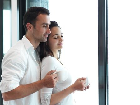 moder: relaxet young couple drink first morning coffee  over big bright window in moder home villa indoors Stock Photo