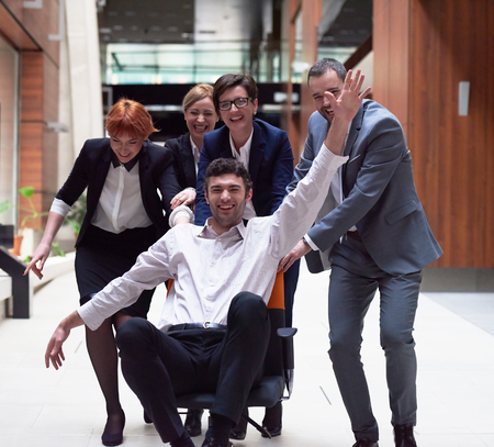 young businessman: business people group at modern office indoors have fun and push office chair on corridor