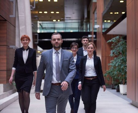 multitud gente: young business people team walking, group of people on modern office hall interior
