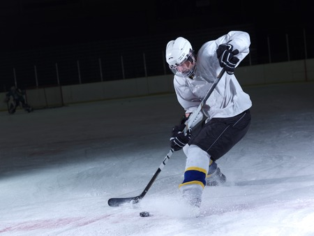 hockey skates: ice hockey player in action kicking with stick