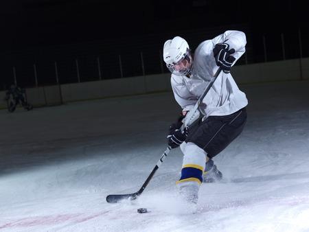 in action: jugador de hockey sobre hielo en la acción patadas con palo