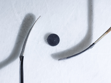 two hockey sticsk and puck on ice, start of the game, competition concept in business, top view Archivio Fotografico