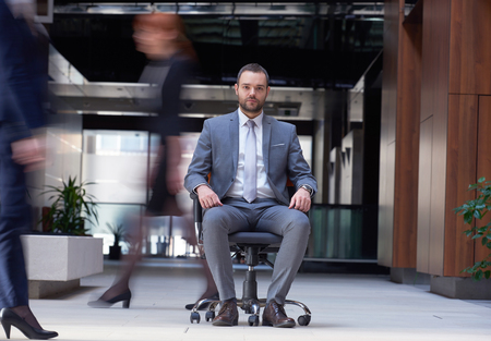 people from behind: business man sitting in office chair,  people group  passing by: Concept of time, rush, organization