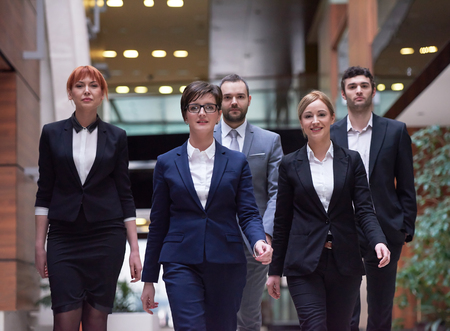 modern office: young business people team walking, group of people on modern office hall interior