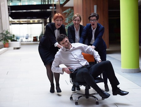 fun at work: business people group at modern office indoors have fun and push office chair on corridor