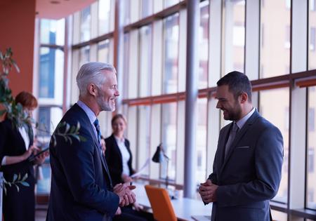 gente trabajando: grupo de personas de negocios con los adultos jóvenes y de alto nivel sobre la reunión en la oficina moderna interior brillante.