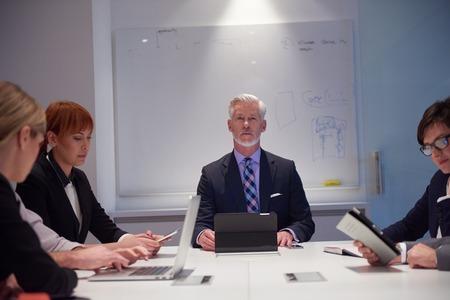 reuniones empresariales: grupo de personas de negocios con los adultos jóvenes y de alto nivel sobre la reunión en la oficina moderna interior brillante.