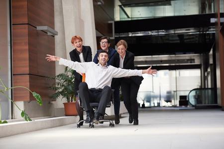 personas en la calle: grupo de personas de negocios en el interior de oficinas modernos divertirse y empuje la silla de oficina en el corredor