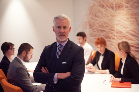 senior business: senior businessman with his team at modern office. business people group