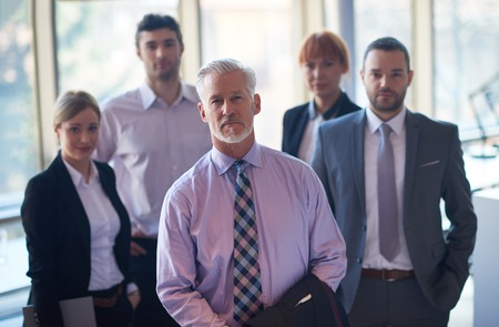 happy workers: senior businessman with his team at office. business people group