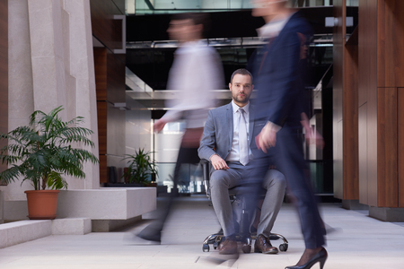 sitting people: business man sitting in office chair,  people group  passing by: Concept of time, rush, organization