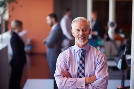 personen: senior zakenman met zijn team op kantoor. bedrijfsmensengroep