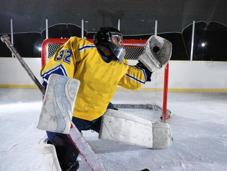goalkeeper: ice hockey goalkeeper  player on goal in action