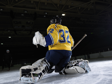 ice hockey: ice hockey goalkeeper  player on goal in action