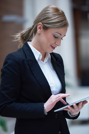 woman business suit: corporate business woman working on tablet computer  at modern office interior