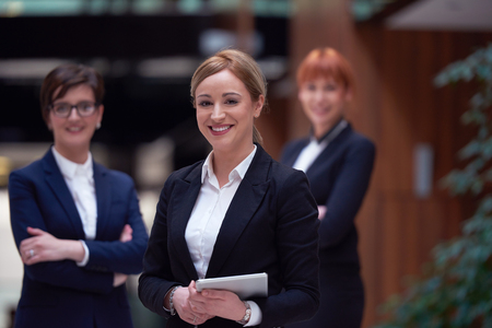 team leader: young business woman group,  team standing in modern bright office and working on tablet computer Stock Photo