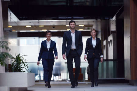 office man: young business people team walking, group of people on modern office hall interior