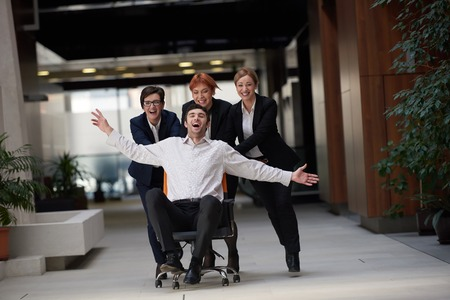 office break: business people group at modern office indoors have fun and push office chair on corridor