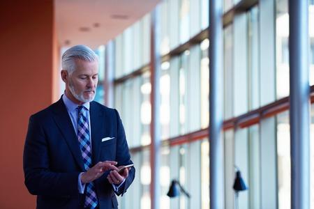 bel homme: homme d'affaires senior parle sur t�l�phone mobile � l'int�rieur de bureaux moderne et lumineux