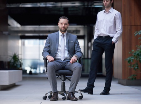 office man: business man sitting in office chair,  people group  passing by: Concept of time, rush, organization